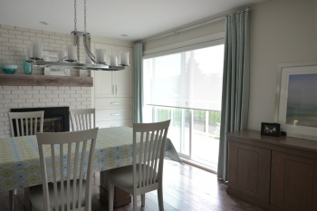 Printed drapes framing sheer roller shades for patio door | The Well Dressed Window - Hunter Douglas Blinds