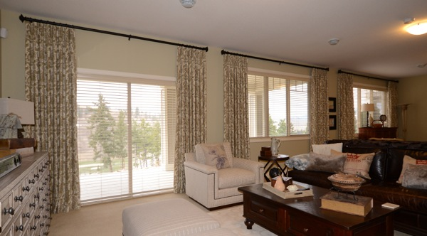 printed drapes framing blinds in living room