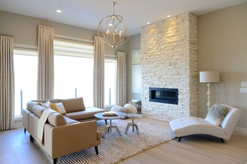 Custom cream drapes in neutral living room with stone fireplace