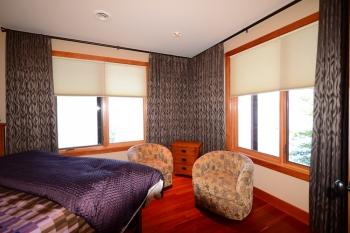 Hunter Douglas Window Treatments Kelowna | Custom blackout drapery for corner window in bedroom